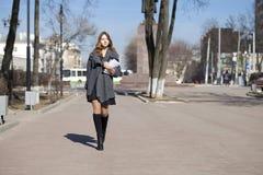 走在春天晴朗的街道上的女小学生 免版税库存图片