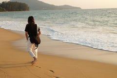 走在晚上时间和小波浪impac的海滩的女孩 免版税库存图片