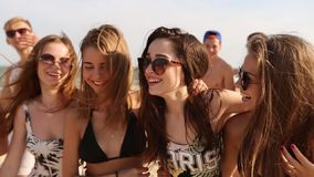 走在晴朗的海滩的小组朋友 年轻人晒黑了走,聊天和笑由海的快乐的白种人人民  股票录像