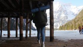 走在有一个大背包的一个lago di braies湖的年轻女人 股票视频