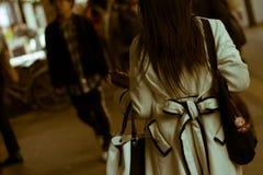 走在有一个电话的一条拥挤街道上的现代繁忙的日本妇女在她的手上 库存图片