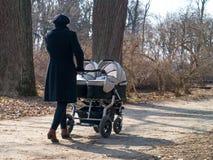 走在有一辆双重双婴儿推车的公园的活跃妈妈与 图库摄影