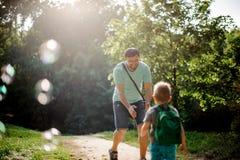 走在有他的小儿子的夏天公园的愉快的父亲 图库摄影
