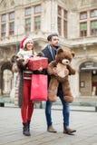 走在有圣诞节礼物的一条街道上的美好的夫妇 免版税库存图片
