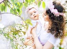 走在有女儿的果树园的迷人的母亲 库存图片