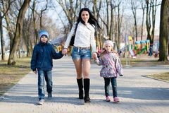走在有她儿子和女儿在春天或秋天的愉快的微笑的&看的公园的妈妈照相机 库存图片