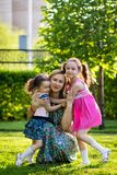 走在有她的母亲的草坪的滑稽的女孩 姐妹与妈妈一起使用 孕产照顾 E 免版税库存图片