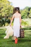 走在有手提箱和玩具熊的公园的女孩 库存照片