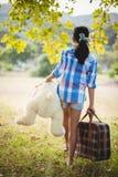 走在有手提箱和玩具熊的公园的女孩 免版税库存照片