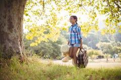 走在有手提箱和玩具熊的公园的女孩 免版税图库摄影