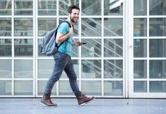 走在有手机和袋子的边路的年轻人 库存照片