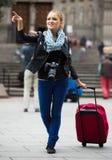 走在有数字照相机的秋天城市的妇女 图库摄影