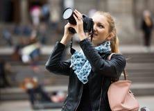 走在有数字照相机的秋天城市的妇女 免版税库存图片