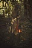 走在有灯笼的一个森林里的妇女 免版税库存图片