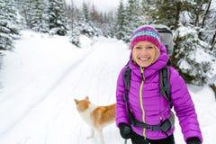 走在有狗的冬天森林里的愉快的妇女 库存图片