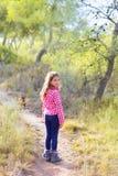 走在有狗的杉木森林里的儿童女孩 图库摄影