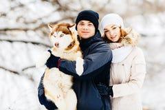 走在有狗红色爱斯基摩的森林里的一对年轻夫妇 定调子 库存照片