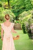 走在有玫瑰的庭院里的维多利亚女王时代的妇女 免版税库存照片
