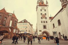 走在有老大厦、商店和塔的历史城市的愉快的人民 免版税图库摄影