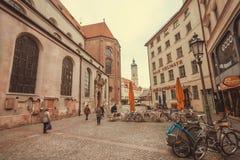 走在有老大厦、商店和被修补的街道的历史城市的人们 免版税图库摄影