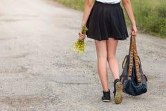 走在有背包旅行概念的路的少妇 免版税图库摄影