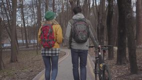 走在有背包的公园的年轻游人在他们的后面 人带领自行车和妇女以明亮的黄色 股票录像