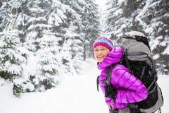 走在有背包的冬天森林里的愉快的妇女 免版税库存图片