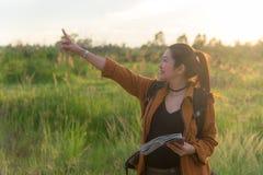 走在有背包的国家公园的远足者亚裔妇女 妇女游人去的野营在草甸森林,日落黑地面里 免版税库存照片