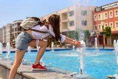 走在有背包的城市附近的背包徒步旅行者女孩,使用用在喷泉的水 免版税库存照片