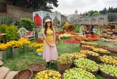 走在有苹果和花收获的草坪的可爱的女孩  免版税图库摄影
