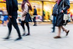 走在有行动迷离的购物街道上的人们 免版税库存图片