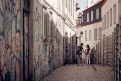走在有街道画的狭窄的街道的可爱的夫妇 库存图片