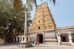 走在有被雕刻的gopuram门的famouse印度寺庙附近的人们 免版税库存照片