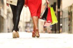 走在有购物带来的街道的两条shooper腿 免版税库存照片