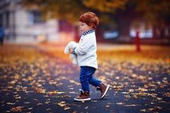 走在有长毛绒玩具的秋天公园的逗人喜爱的红头发人小孩男婴在手上 免版税库存图片