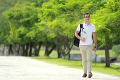 走在有backpac的学院公园的英俊的大学生 免版税库存图片