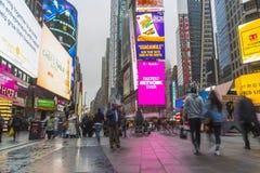 走在有LED的时代广场的拥挤游人签字 库存图片