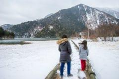 走在木板走道的两个女孩由雪和风的湖 免版税库存照片