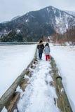 走在木板走道的两个女孩由雪的湖 库存图片