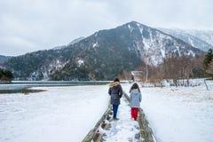 走在木板走道的两个女孩由雪的湖 免版税库存照片