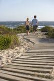 走在木板走道的男孩和女孩往海 免版税库存图片
