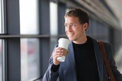 走在机场的商人饮用的咖啡 免版税库存照片