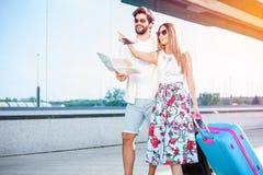 走在机场终端大厦前面的年轻夫妇,拉扯手提箱 库存图片