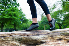 走在树干的妇女的脚 免版税库存照片