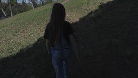 走在树附近和由小山决定的女孩 股票视频