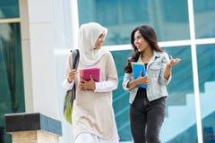 走在校园里的两个亚洲人学生 图库摄影