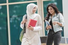 走在校园里的两个亚洲人学生 免版税库存照片
