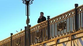 走在桥梁和谈话的年轻人在电话日落射击 影视素材