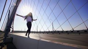走在桥梁栏杆的女孩分开涂他的手在慢动作 股票视频