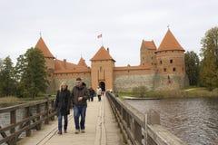 走在桥梁的人们到特拉凯海岛城堡 免版税库存图片